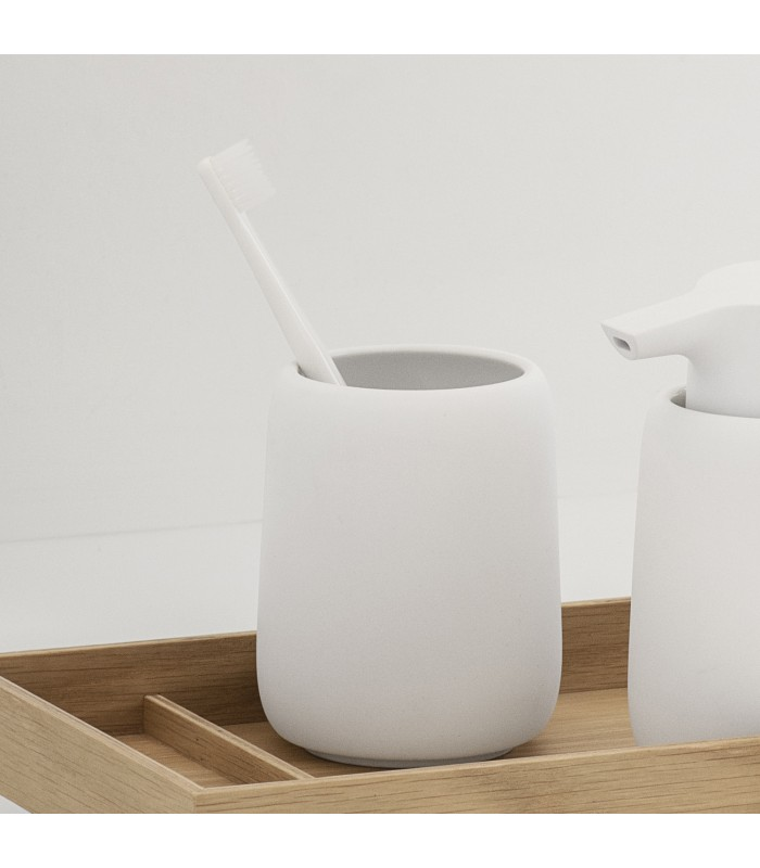 white tumbler for toothbrushes in bathroom
